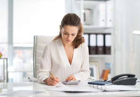 An elegant businesswoman is concentrating while sitting at her desk in a modern office, crunching numbers. Stock Photo