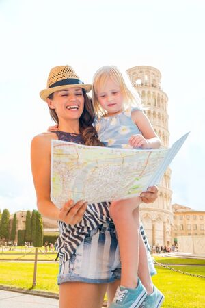 A mother holding her blonde daughter in her arms smiles and laughs as they look at a map of Pisa. Behind them, the Leaning Tower of Pisa. Stock Photo