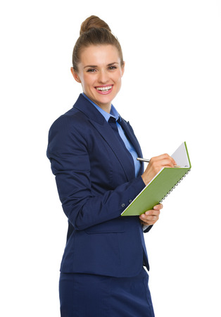 An elegant businesswoman is standing, smiling happily. She has paused from taking notes in her handy notebook. Stock Photo