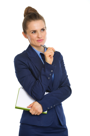 An elegant businesswoman stands thinking, holding a notebook tucked under one arm, and resting her pen against her chin. She is deep in thought, looking into the distance.