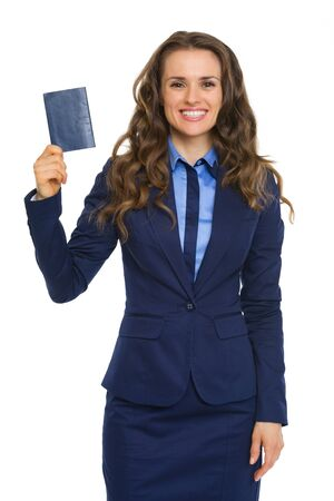 An elegant brunette wearing a suit is smiling, holding up a blue passport. Stock Photo