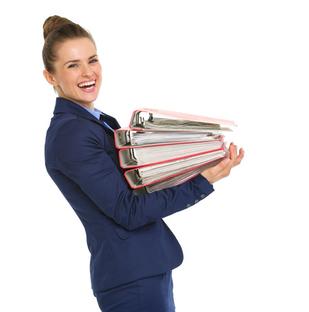 A happy woman in profile is smiling over her shoulder. In her arms, she is carrying a stack of folders filled with papers. Stock Photo
