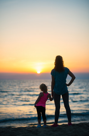 silently: A mother and young daughter hold hands, silently looking out as the sun disappears into the sea on the horizon. Sundown at the beach is such a magical time. Stock Photo