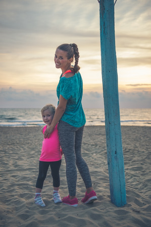 A lovely young mother is standing on the beach at sundown. She is looking over her shoulder, smiling, and lovingly holding her daughter who is standing next to her. Stock Photo