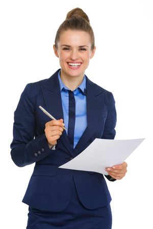 An elegant businesswoman is looking up and smiling. In her hands, she is holding a document. In the other hand, she is holding a pen. Stock Photo