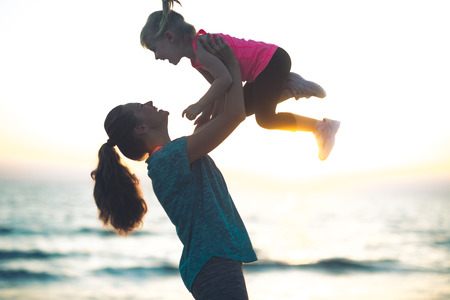 A mother with her hair pulled back in a ponytail is lovingly throwing her child up in the air at sundown. You can practically hear the joyful giggles...