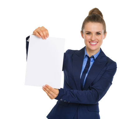 An elegant, smiling business woman is holding up a blank piece of paper with both hands.
