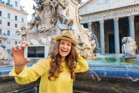 giggling: A laughing brunette holds up her mobile phone and is smiling and giggling while trying to take a selfie. Behind her, Romes Pantheon fountain and Pantheon.