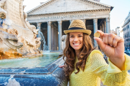 At the Pantheon fountain and Pantheon in summer, a smiling brunette tourist holds a coin up as she prepares to throw it into the Pantheon fountain to make a wish.