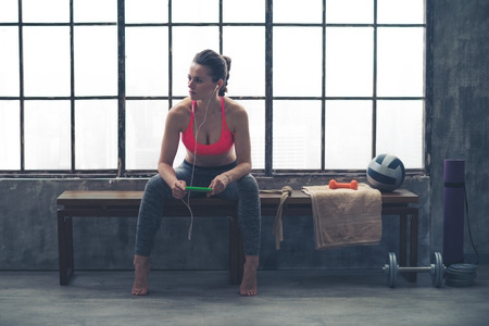 gym room: an athletic woman watches something in the distance. She is sitting on a bench by a window in a loft gym, holding her device and listening to music.