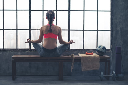 gym room: As the city bustles below, this fit, athletic woman sits quietly meditating in lotus position on a wooden bench. Stock Photo