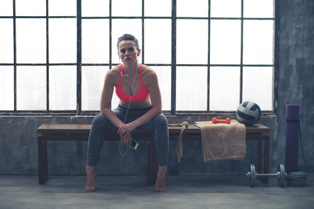 gym room: Resting her elbows on her knees, a young, athletic woman is sitting relaxing, resting in between workouts... Stock Photo