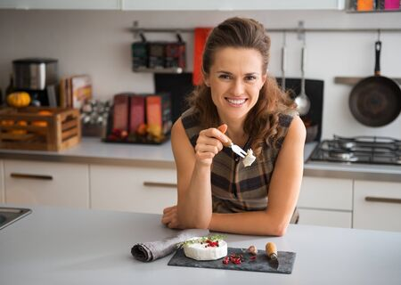 joys: It is the simple joys in life that are so delicious. Here, an elegant woman is leaning on her kitchen counter, holding a slice of fresh Camembert on her cheese fork, getting ready to enjoy it.