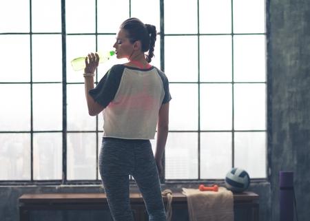 Fit woman in workout gear in profile drinking from water bottle in a loft gym in the city. Foto de archivo
