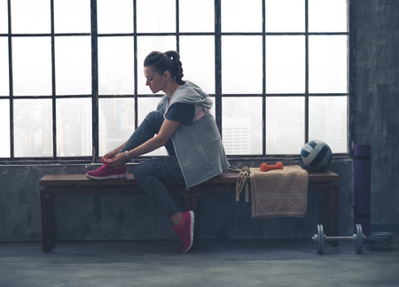 A quiet moment to tie her shoes. A fit, sporty young woman has one foot up on a bench, tying her shoelaces, as she gets ready to start her workout.