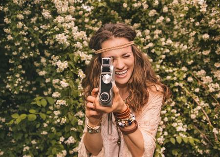 mujer hippie: De pelo largo joven hippy de aspecto en mantón de punto y una blusa blanca que se coloca entre las flores que juegan con la cámara retra
