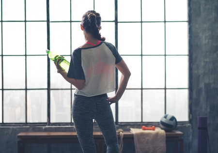 mujeres fitness: Una mujer es relajante, con una botella de agua en una mano mientras mira por la ventana en su gimnasio de loft ciudad.
