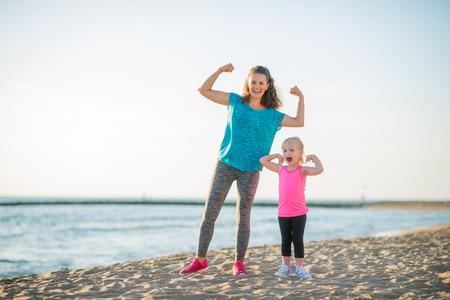 勝利.我々 は両方は水に沿ってレースを獲得しました。よくやった、ママ!よくやった、娘!幸せな母と娘は、自分の腕を屈曲夕暮れ時、ビーチに沿っ
