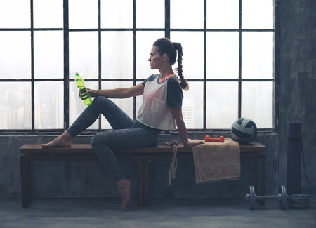 athletic gear: An athletic woman wearing workout gear is sitting relaxing on a wooden bench in a loft gym. Having just finished her yoga workout, she is relaxing and holding a bottle of water. Stock Photo
