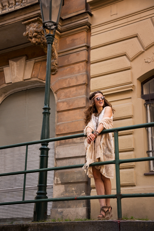 expresses: Longhaired hippy-lookin young lady in jeans shorts, knitted shawl and white blouse with sunglasses stands near streetlight in old town looking at skies and expresses surprise