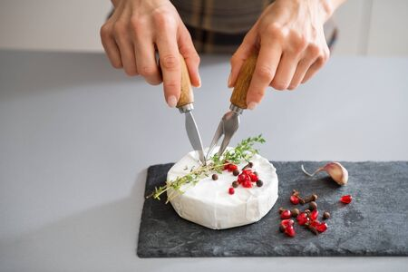 hermelin: A fresh Camembert sits on a slate board. It is decorated with a sprig of fresh rosemary and a few pomegranate seeds. Here, a womans hands are cutting into the cheese, preparing it to be served. Stock Photo