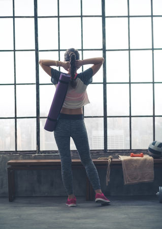 linked hands: A fit young woman is standing looking out of the window from a cool city loft gym, where she has just enjoyed an intense workout. Her hands are linked behind her head, as she stretches and relaxes. Stock Photo