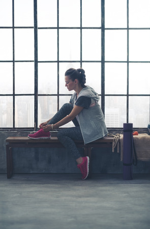 quiet: A quiet moment to tie her shoes. A fit, sporty young woman has one foot up on a bench, tying her shoelaces, as she gets ready to start her workout.