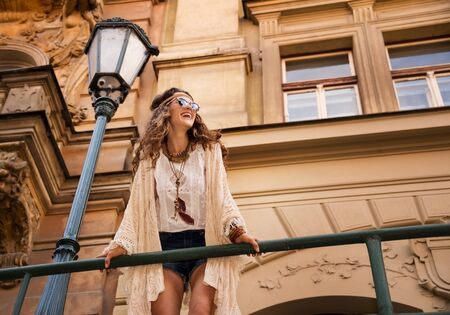 Longhaired hippy-lookin young lady in jeans shorts, knitted shawl and white blouse with sunglasses stands near streetlight in old town looking at skies and smiling