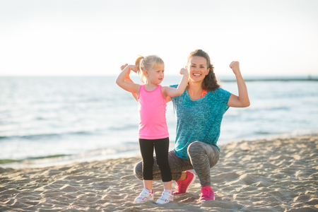 A happy young mother and daughter wearing workout gear are together on the beach at dusk. The mother is kneeling down next to her daughter, and both are flexing their arms to show how strong they are.