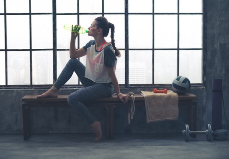 gym room: Fit woman in profile sitting on bench in loft gym drinking water. After a good workout, its important to hydrate.
