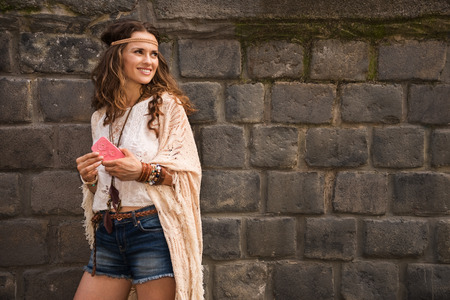 Longhaired hippy-looking young lady in jeans shorts, knitted shawl and white blouse standing near stone wall in old town and holding cell phone