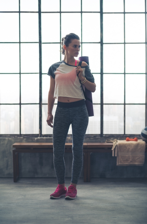 Pensive, a fit woman is standing in front of a wooden bench in a loft gym. With her yoga mat over one shoulder, she is looking off to the side, thinking.