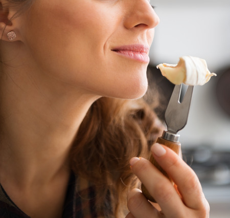 Oh, the rich aroma of a perfectly-ripe Camembert cheese. There is no mistaking that heady smell and wonderful taste. Here, we see a woman smelling the sharp aroma of the cheese she is about to eat. Standard-Bild