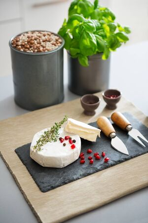 hermelin: The taste of France, right there on a board. A fresh, perfect Camembert cheese sits ready to be eaten on a slate board. It is decorated with fresh rosemary and pomegranate seeds. Stock Photo