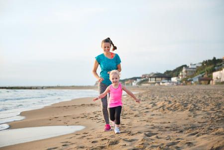 hasten: A young girl is running ahead of her mother on the beach at sunset, delighted to be running faster than her. Laughing and chasing her daughter, this young mother couldnt be happier.