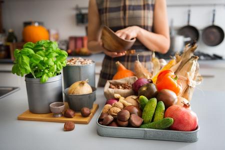 Een dienblad vol herfst vruchten, noten en groenten zit op een aanrecht. Naast de bak, een houten snijplank met een plant verse basilicum en ui beloven een heerlijke maaltijd vooruit. Stockfoto
