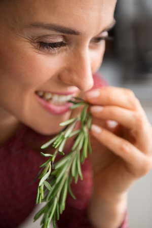 nip: A woman smiles as she takes a little nip of some fresh rosemary. Impossible to resist the rich, earthy flavour of freshly-picked rosemary. The hard part will be deciding which dish to cook... Stock Photo