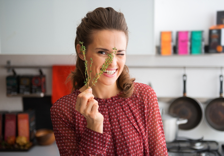 silliness: Who says that silliness isnt the magic ingredient to make every dish a celebration... An elegant woman peeks through a sprig of fresh thyme, laughing, as she prepares a meal.