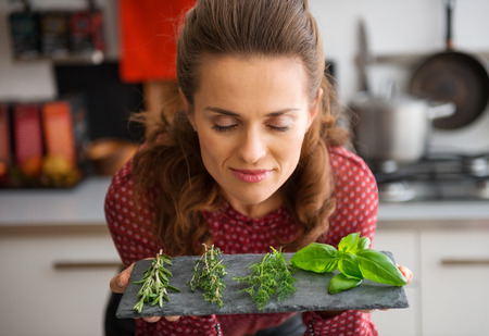 Oh, the heady smell of fresh herbs, conjuring up dreams of all kinds of recipes... A woman, smelling deeply, and closing her eyes in pleasure, leans over a slate showing a few sprigs of fresh herbs. Stock Photo