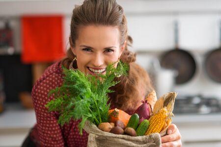 sac: An elegant brunette leans down over a burlap sac of fresh autumn vegetables. Stock Photo