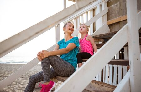 child on beach: A happy mother in fitness gear is sitting with her daughter