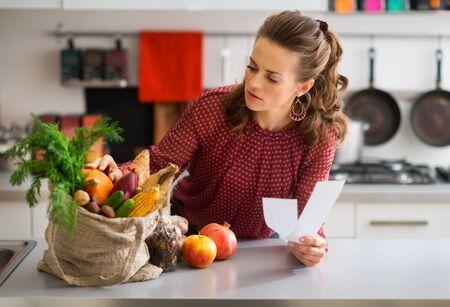 cuerno de la abundancia: Una mujer elegante se apoya en el mostrador de la cocina Foto de archivo