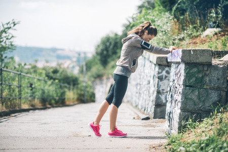 stretch out: Feel that burn, and stretch those muscles... A woman wearing workout gear is using a rock wall to stretch out her legs before starting her run.