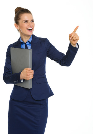 successes: Here, a happy businesswoman holding a file under one arm, and pointing upwards with the other is happy as she points out her successes. Stock Photo