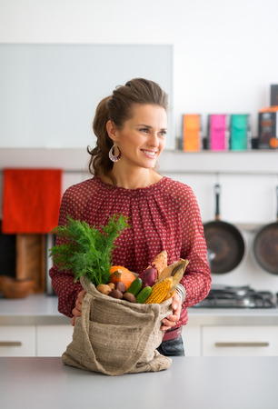 burlap sac: An elegant woman is standing, smiling and looking into the distance. She is holding a burlap sac filled with a variety of fall fruits and vegetables. The colours and flavours of the autumn abound.