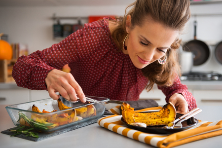 focuses: An elegant woman in a kitchen focuses on serving a slice of roasted pumpkin onto a dark plate. Stock Photo