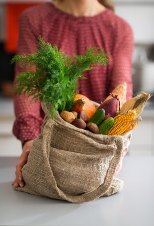 An elegant woman in a kitchen is steadying a full burlap sac of fall vegetables. In the sac, we see corn, sweet potato, pumpkin, onion, carrots, and other fall fruits and nuts.