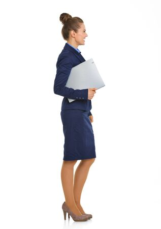 meet and greet: An elegant businesswoman stands in profile. She is looking relaxed and happy. Under her arm, she holds a file, and is ready to meet and greet her meeting partners. Stock Photo