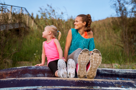 upturned: A young mother and daughter are sitting on an upturned boat. In the foreground, their running shoes.