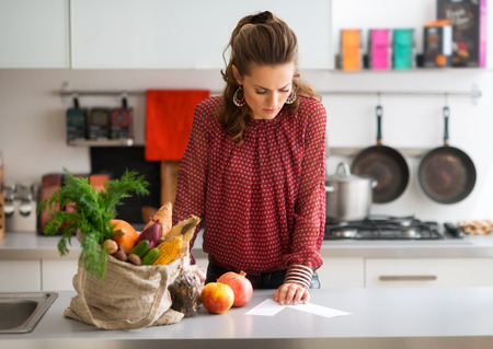 food on table: An elegant woman looks down at the shopping lists on her kitchen counter, reading them carefully. Next to her on the kitchen counter, a burlap sac holds a wide variety of fall fruits and vegetables.